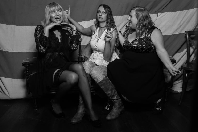 A black and white photo of Gina Christopher, Jessica Taylor, and Katy Ipock sitting on a couch dancing.